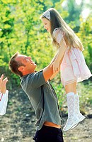 Side view of father holding daughter in air