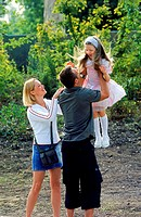 Father mother holding daughter in air