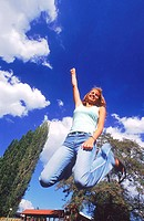 Low angle view of a young woman jumping up in excitement