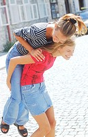 Two young women riding piggyback