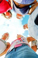 Low angle view of a group of young people standing in a circle (thumbnail)