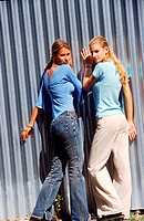 Rear view of two Young women leaning on a wall (thumbnail)
