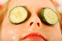 Close-up of a woman´s eyes covered with cucumber slices