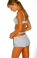 Rear view of a young woman in underwear measuring her waist