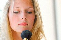 Young woman applying makeup with a brush