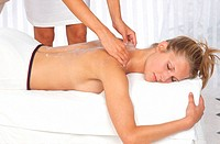 Young woman getting massaged by a female masseuse