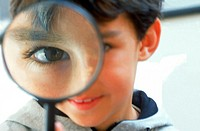 A boy looking through a magnifying glass