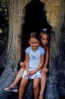 Two girls sitting in a hold in a tree