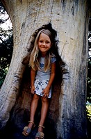 Low angle view of a young girl standing in tree hole