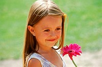 Portrait of a young girl smiling holding a flower