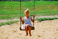 Portrait of a young girl sitting on a swing