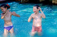 Two kids playing with water in a swimming pool