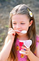 Close-up of a girl eating flavored yoghurt