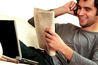 Close-up of a young man reading a newspaper and talking on a mobile phone (thumbnail)