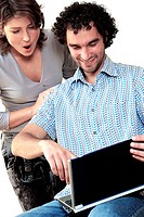 Young woman standing behind a young man working on a laptop