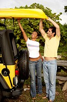 Young woman and a mid adult man loading a kayak on a jeep