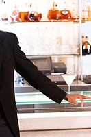 Mid section view of a businessman standing at a bar counter
