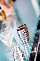Close-up of two martini glasses with cocktail shakers on a bar counter
