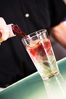 Mid section view of a man preparing a cocktail