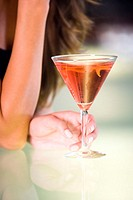 Close-up of a young woman's hand holding a glass of martini