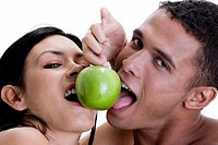 Portrait of a young couple sharing a green apple