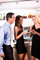 Mid adult man standing with two young women near a bar counter