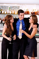 Businessman with his arms around a young woman and a mid adult woman