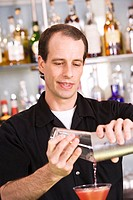 Close-up of a mid adult man preparing a cocktail