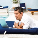 Side profile of a mid adult man using a laptop