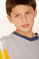 Close-up of a boy holding a glass of orange juice