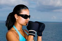 Close-up of a young woman wearing boxing gloves