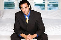 Portrait of a businessman sitting on a bed (thumbnail)