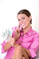 Portrait of a young woman talking on a mobile phone and holding US paper currency