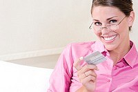 Portrait of a young woman holding a credit card