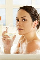 Side profile of a young woman holding a glass of wine in a bathtub