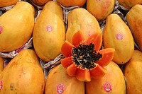 Papayas on display at a market. Papayas are a tropical fruit. One has been cut open (lower right) to reveal the seeds (black) and the edible flesh. Ph...