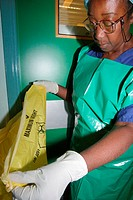 Hospital hygiene. Hospital cleaner using a yellow refuse bag. The markings on the bag indicate that it contains medical waste.