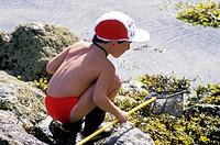 Rock pool fishing. Young boy fishing in a rock pool.