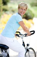 Cyclist. Smiling woman enjoying a cycle ride in the countryside.