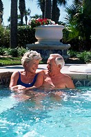 Senior couple smiling in swimming pool