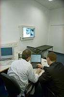 Rear view of two doctors using laptop