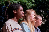 Multiracial group of teenagers standing together staring into distance,