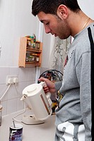 Young man in the kitchen making a mug of coffee,  for use in HIV and Aids,