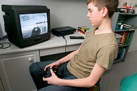 Boy playing a computer game in his bedroom,