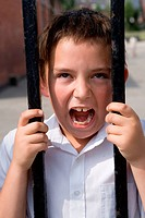 Boy making a face through the fence out of the school playground,