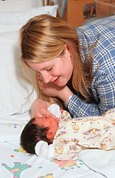 Young teenage mother looking at new born baby smiling,
