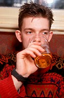 Young man drinking beer in pub,