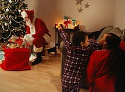 Children (6-7) finding Santa Claus by Christmas tree