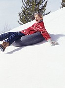 Girl (6-7) sliding down snow slope on inner tube