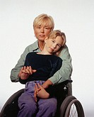 Mother embracing daughter (13-14) in wheel chair, posing in studio, portrait